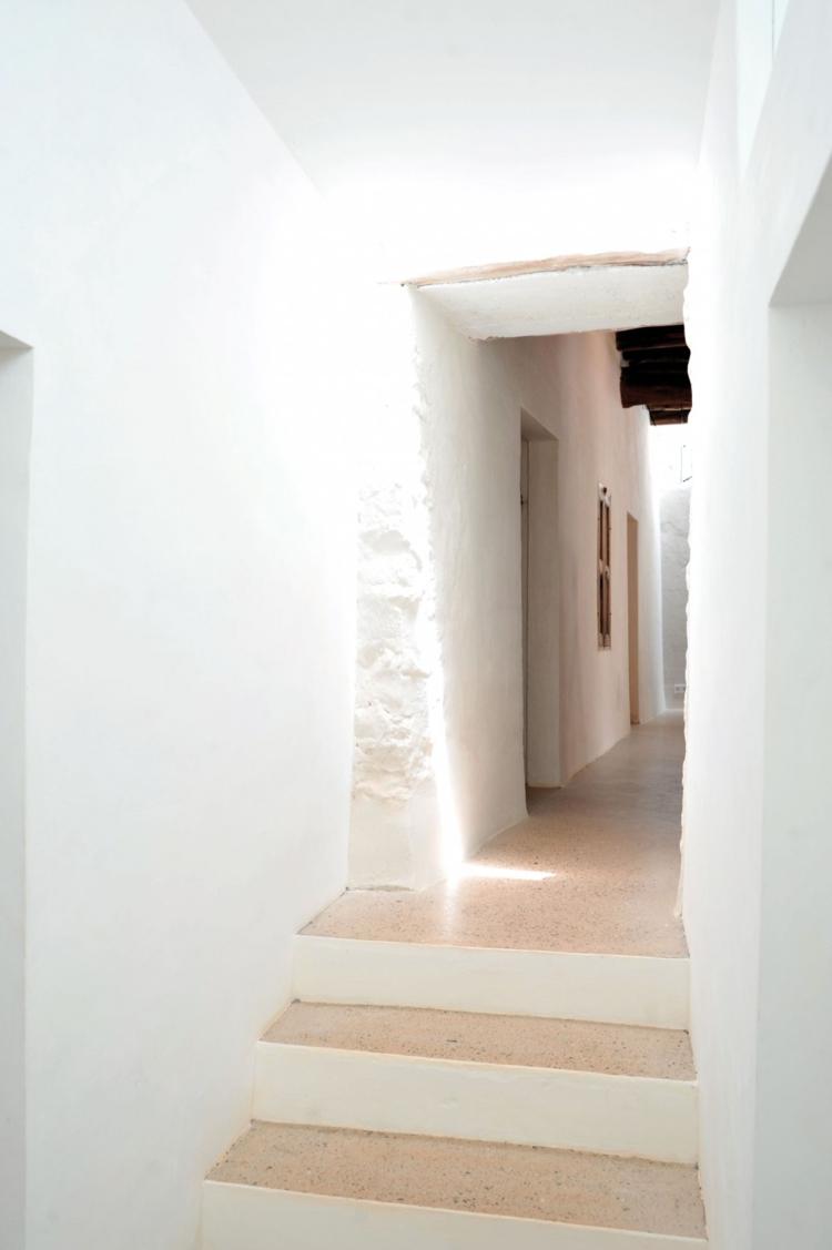 Mur en pierre apparente mobilier en bois et plafond en poutres