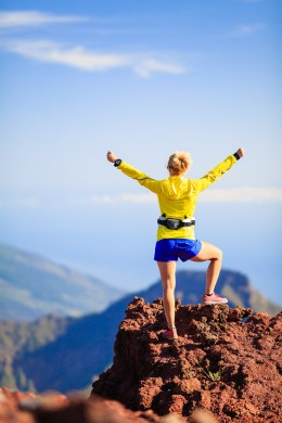 Climbing hiking or trail cross country running woman and success in mountains. Fitness and healthy lifestyle outdoors in summer nature. Achievement and motivation reaching goals outside with arms outstretched.