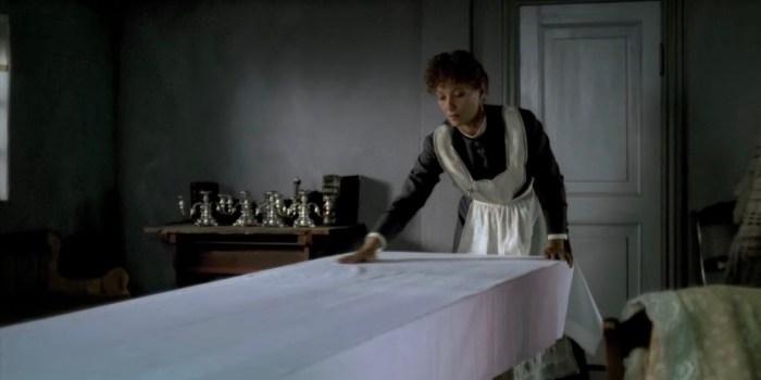 vrouw in donkere kamer die de tafel dekt