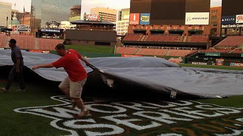 Colocación de lona para proteger el infield del terreno del Estadio Busch de San Luis
