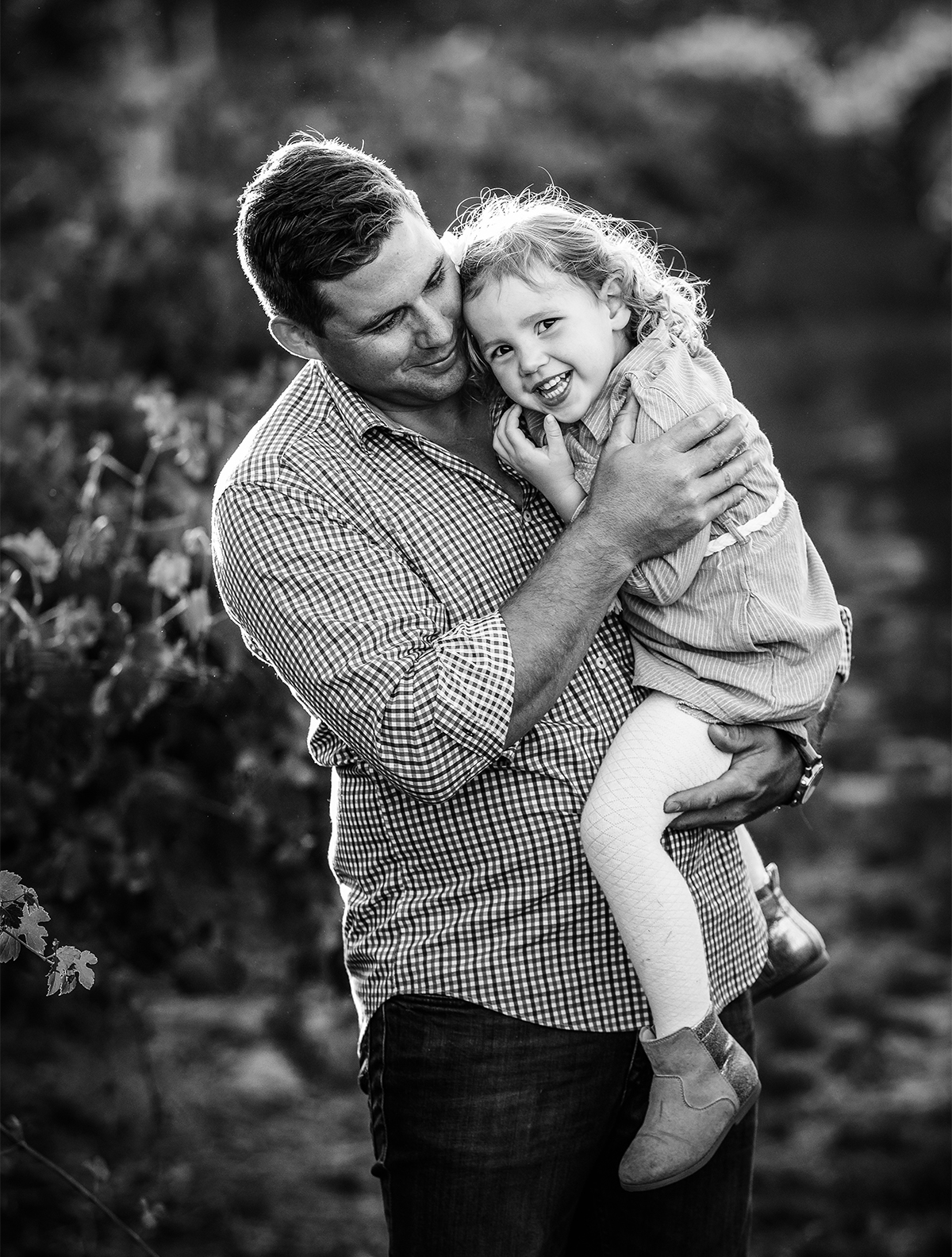 daddy cuddling daughter in the vineyards at their family photo session by deb elton photgraphy