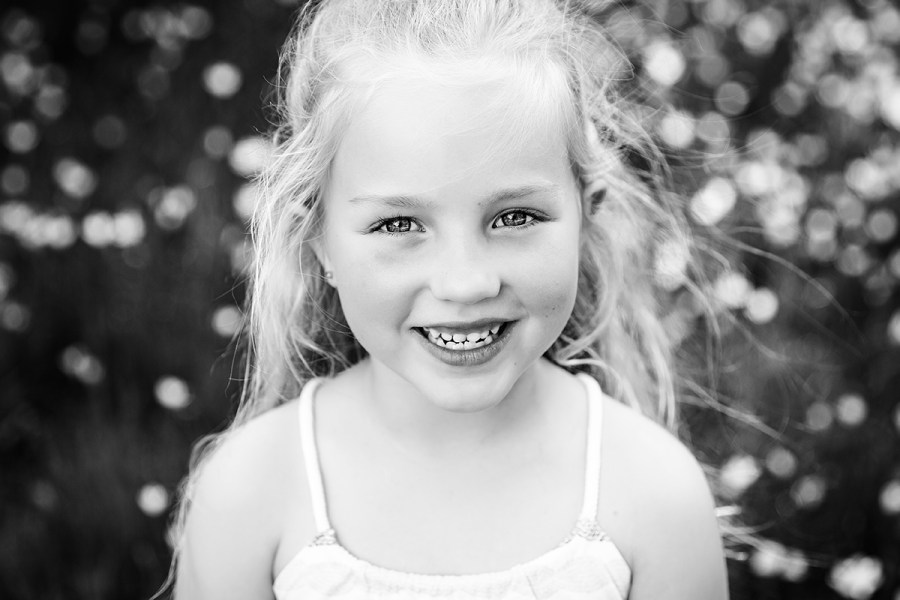 little girl smiling at her family photo session in the forest by deb elton photography