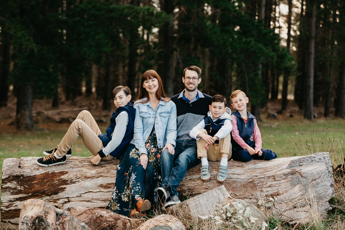family with 3 boys sitting on a log in the forest for a family photo session
