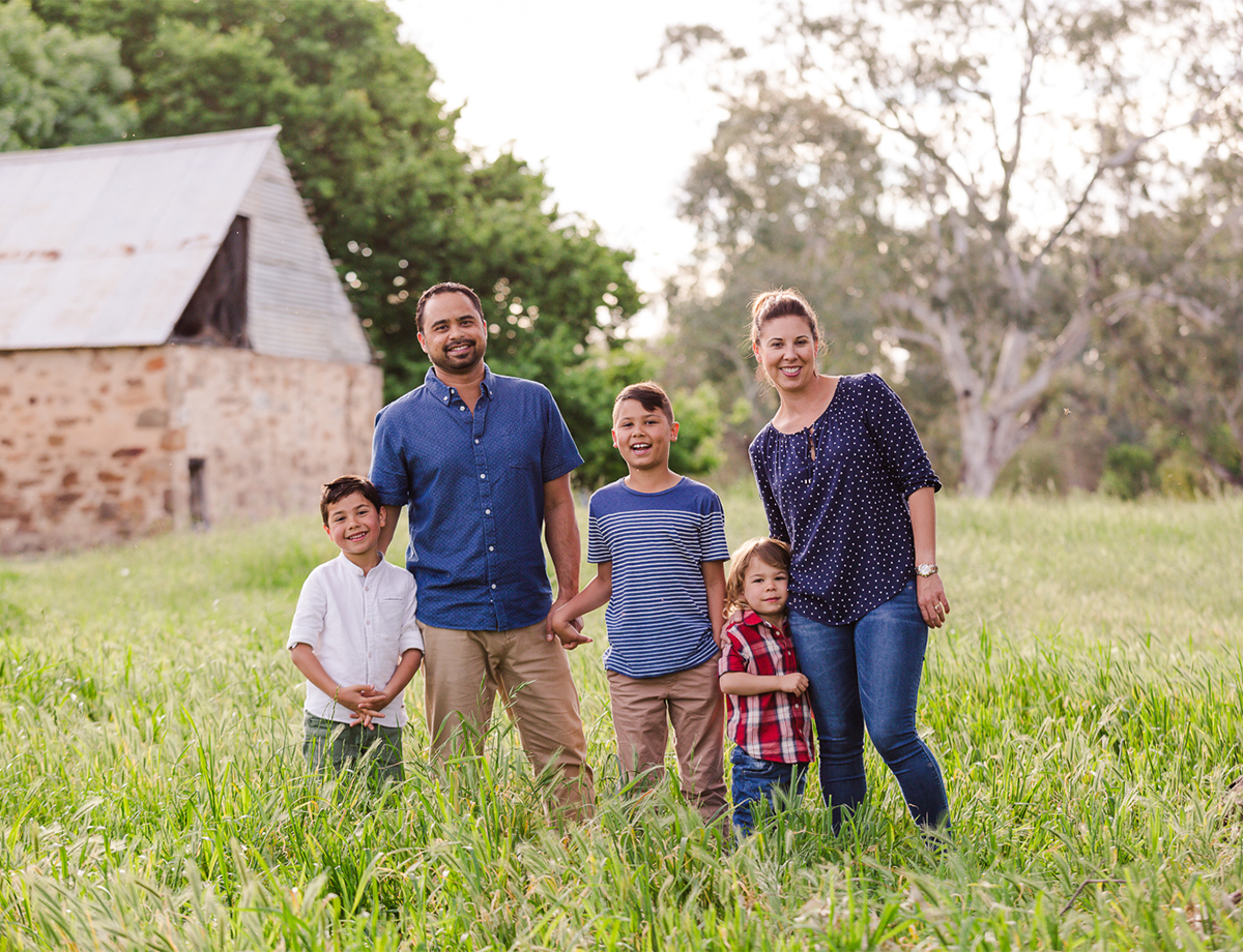 family in a field smiling laughing at their family photo session by deb elton photography