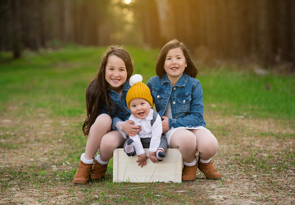 sisters and baby sitting on a box in the forest for a family photo session