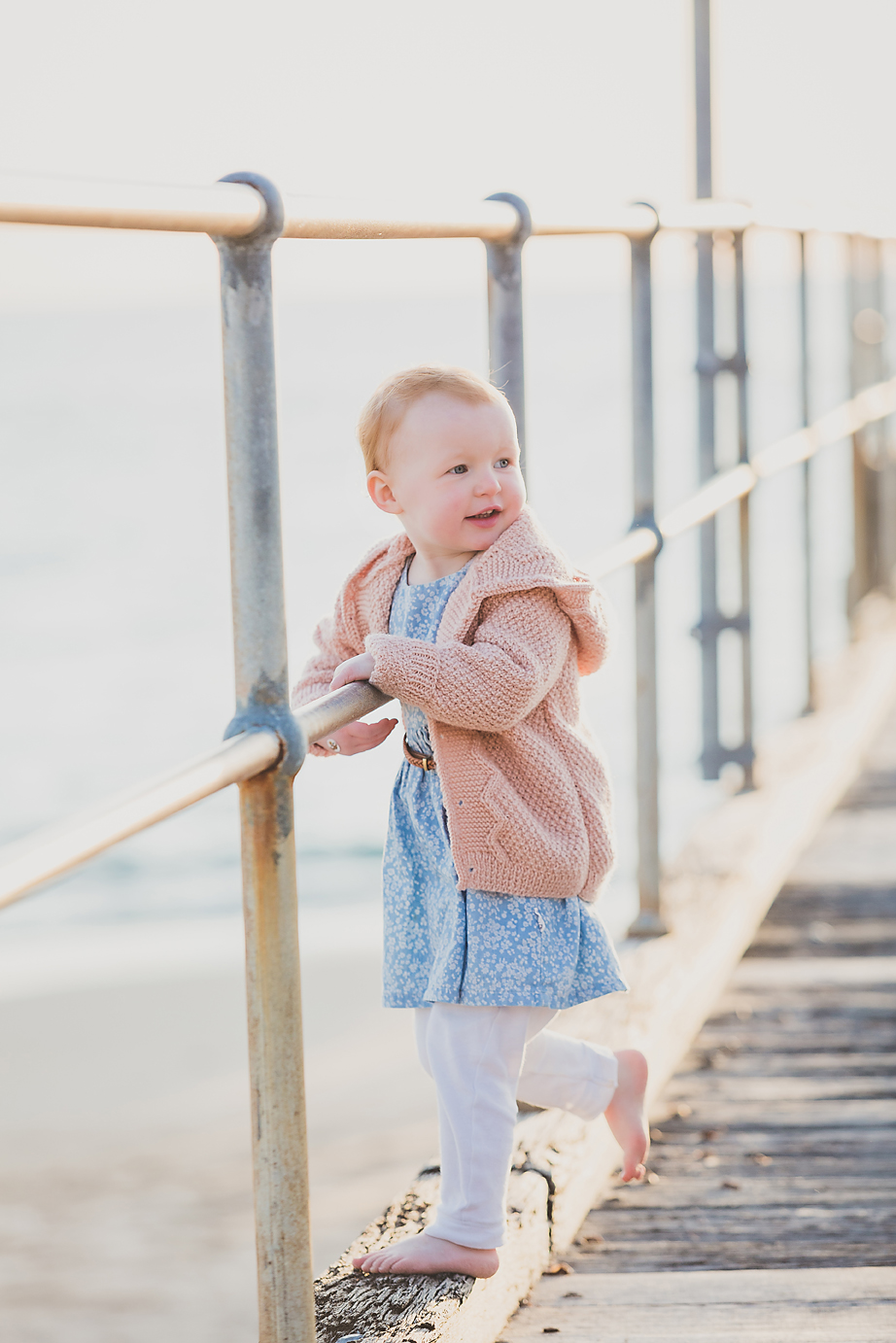 little toddler girl standing on the jetty at the beach