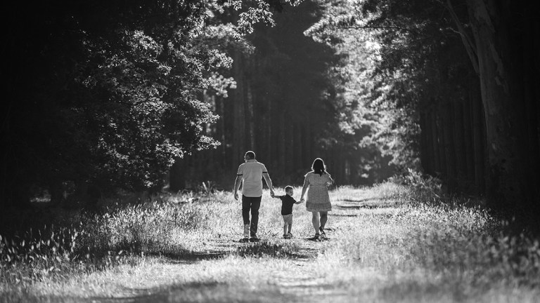mum and dad walking with little boy in the forest for a family photo session