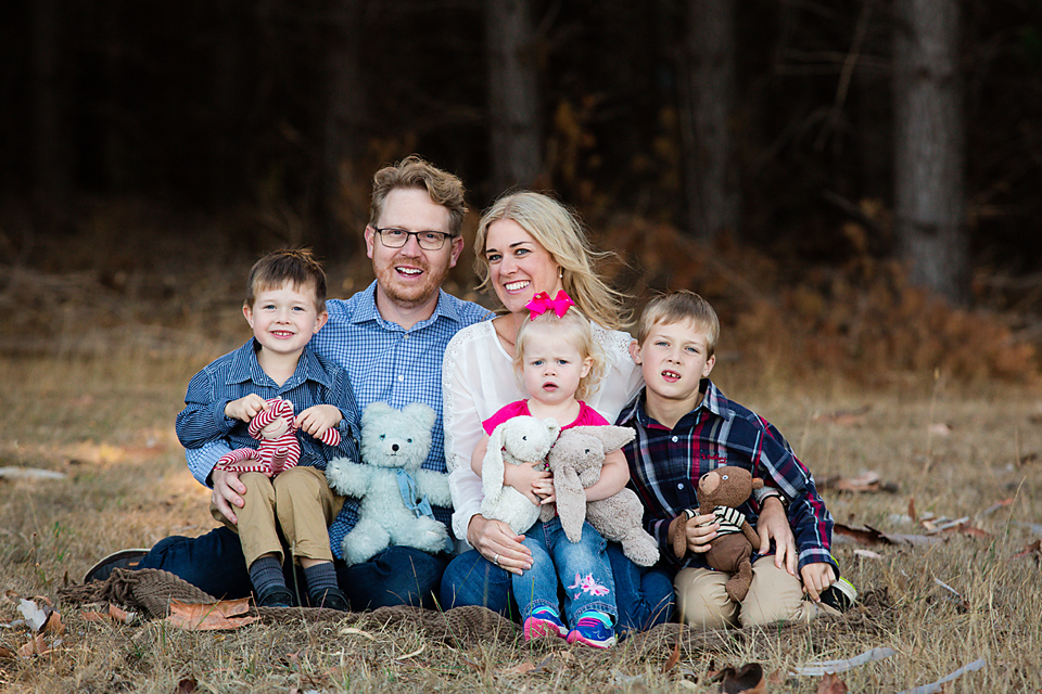 family sitting on a rug with their kids and their soft toys for a family photo session