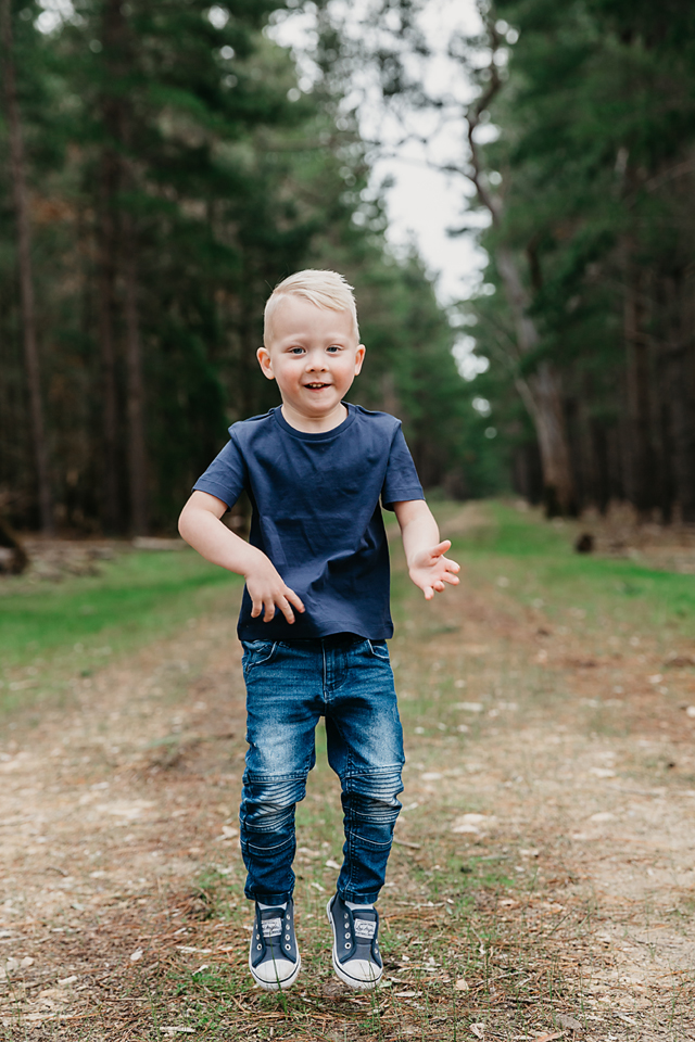boy jumping in the forest for a family photo session
