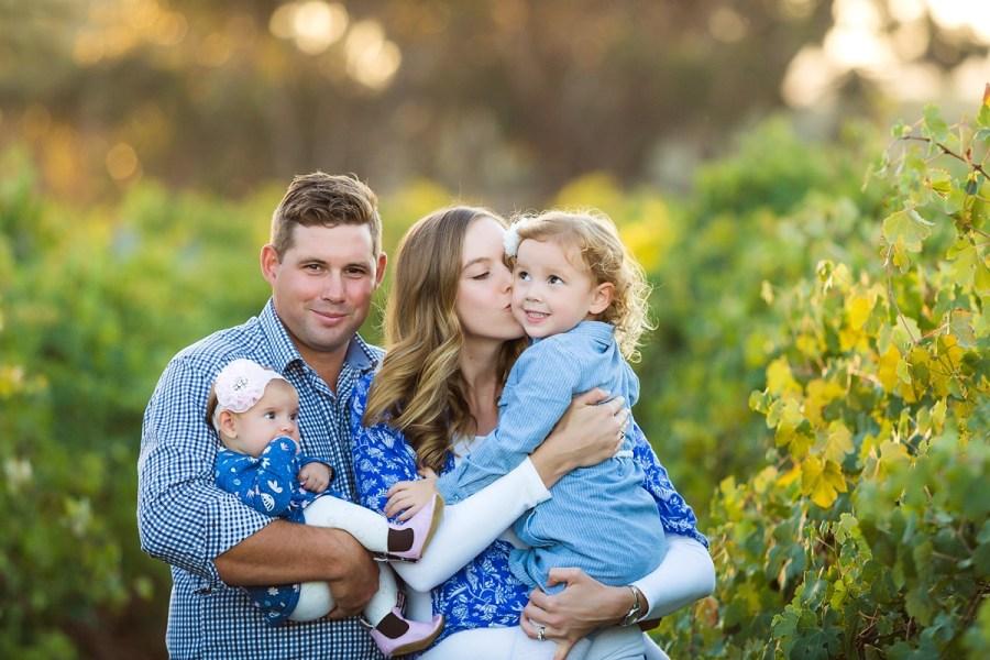family cuddling in vineyards