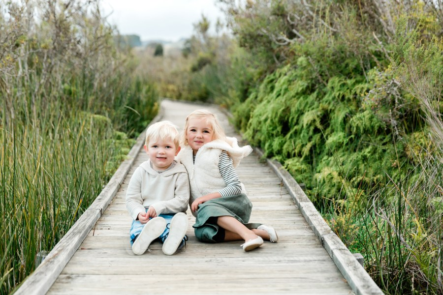 toddlers sitting on a boardwalk