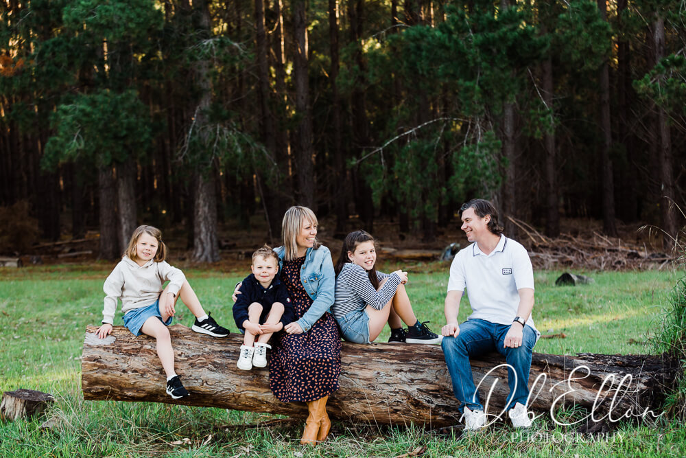 family sitting on log in forest