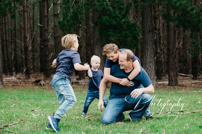 dad and his boys jumping on him and wrestling for a family photo session