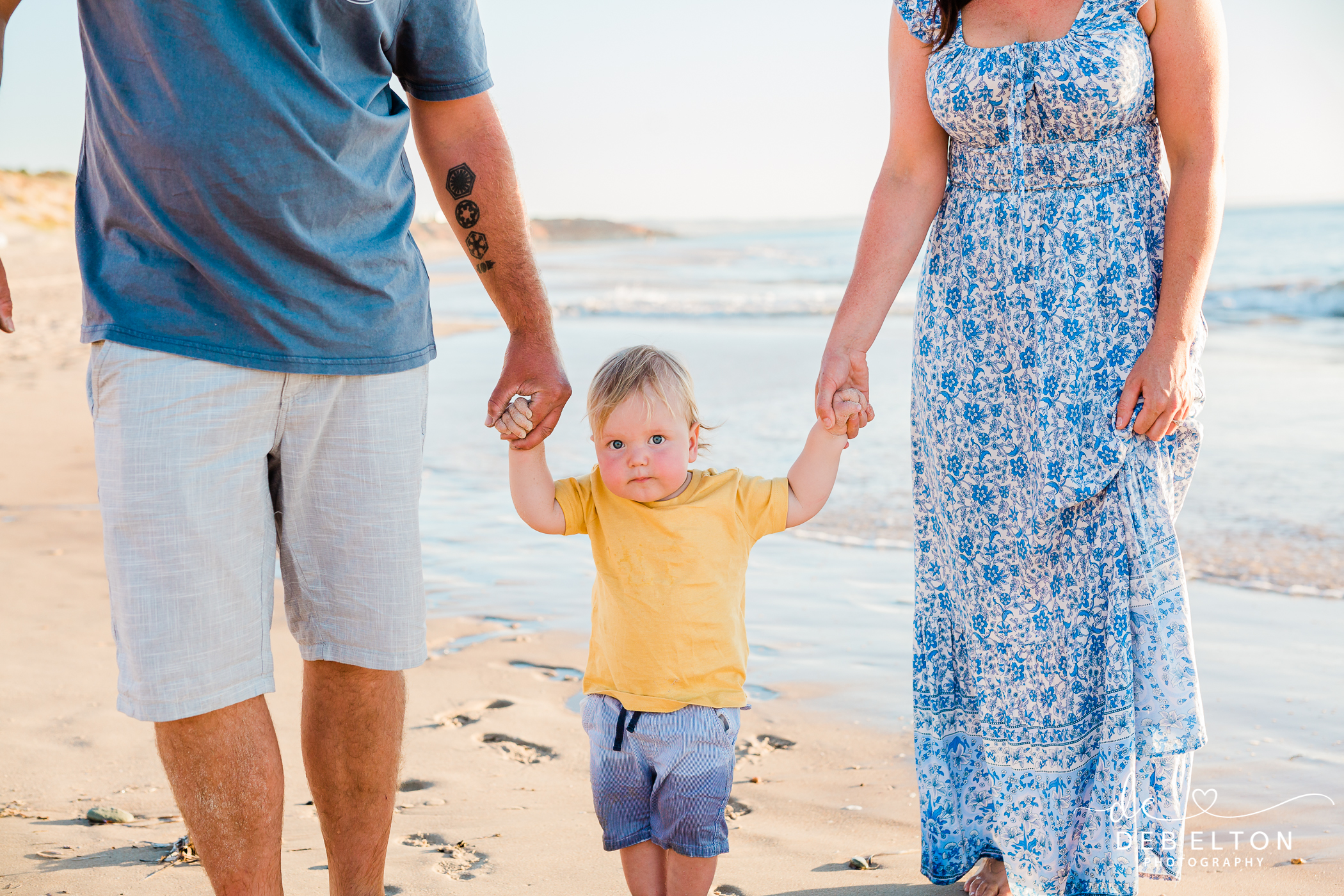 boy toddler holding mum and dads hand on the beach