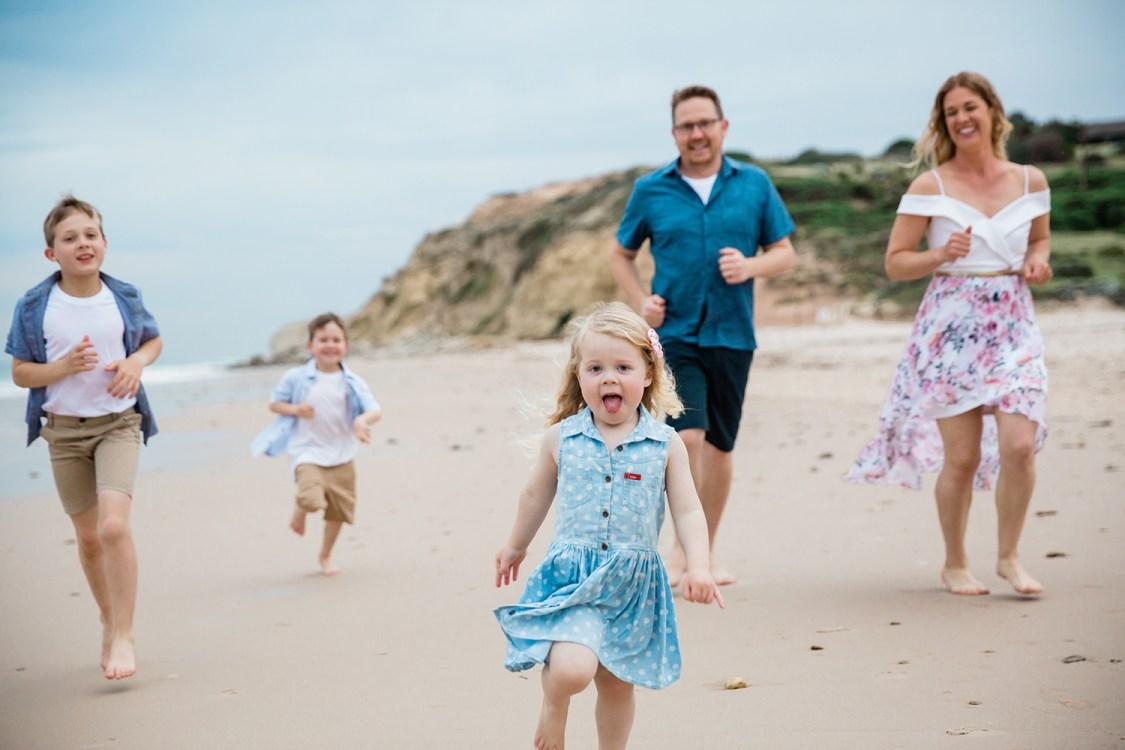 family running along the beach