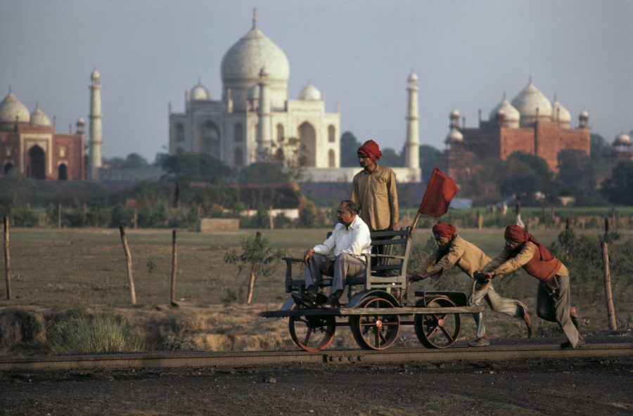 Railroad line inspector being pushed by a retinue of workers to check for wear and tear on the tracks, Agra, India, 1983