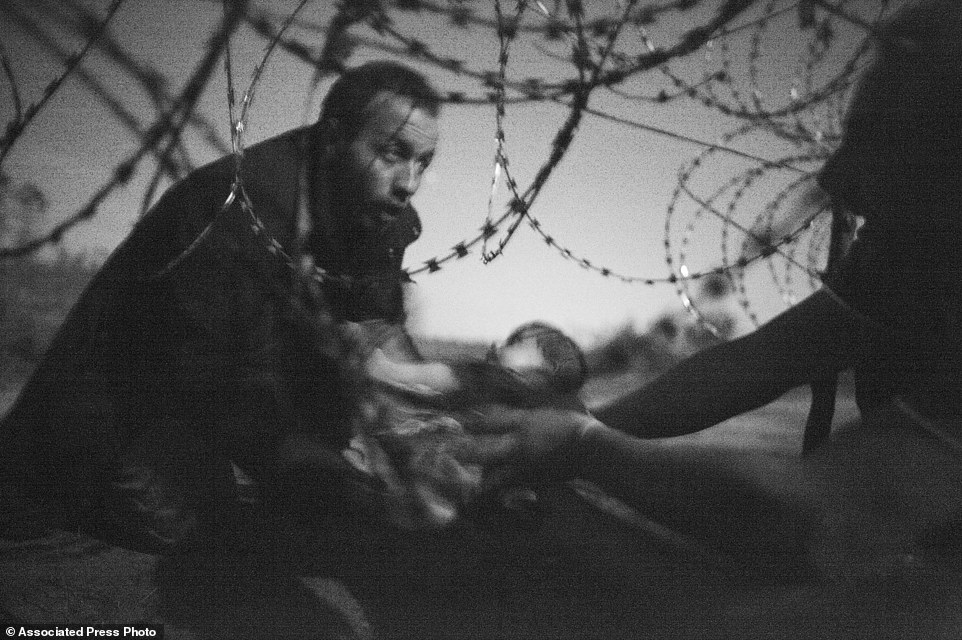 "In this image released by World Press Photo shows the World Press Photo of the Year titled ""Hope for a new Life"" by photographer Warren Richardson. The picture also won a first prize in the Spot News singles category and shows a man passing a baby through the fence at the Serbia-Hungary border in Roszke, Hungary, Aug. 28, 2015. (Warren Richardson, World Press Photo via AP)"
