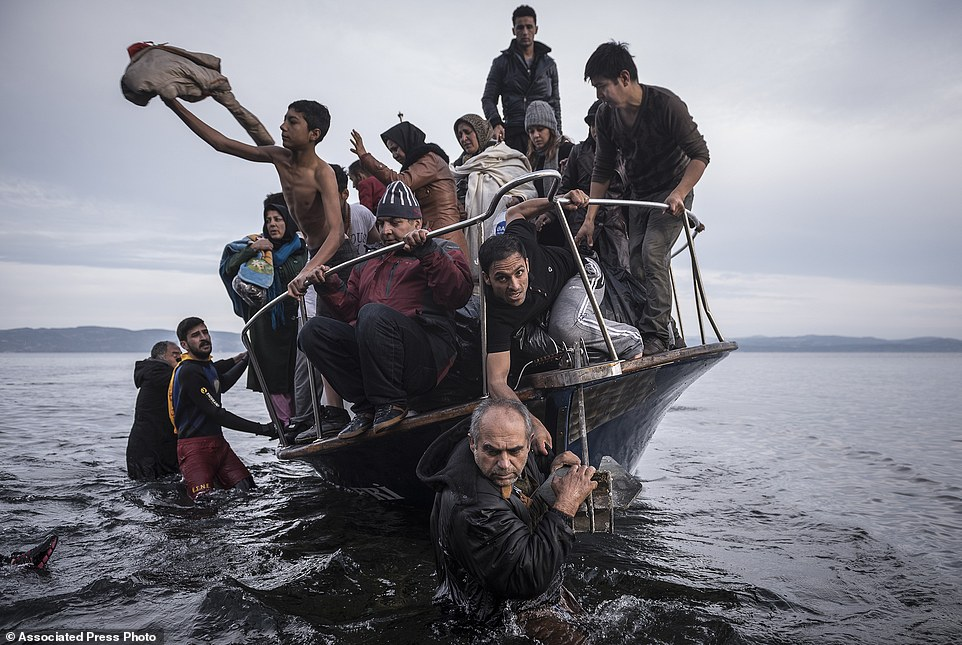 "In this image released by World Press Photo titled ""Reporting Europe's Refugee Crisis"" by photographer Sergey Ponomarev for The New York Times which won the first prize in the General News Stories category shows refugees arriving by boat near the village of Skala on Lesbos, Greece, 16 November 2015. (Sergey Ponomarev for The New York Times, World Press Photo via AP)"