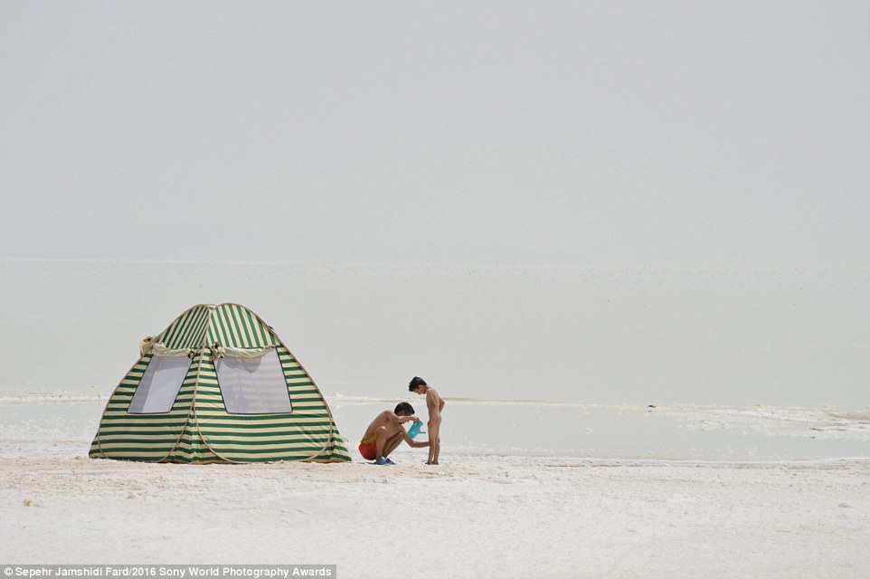 32A2C6FC00000578-0-A_father_cleans_the_salt_from_his_son_after_a_swim_in_the_Orumiy-a-30_1459260734104