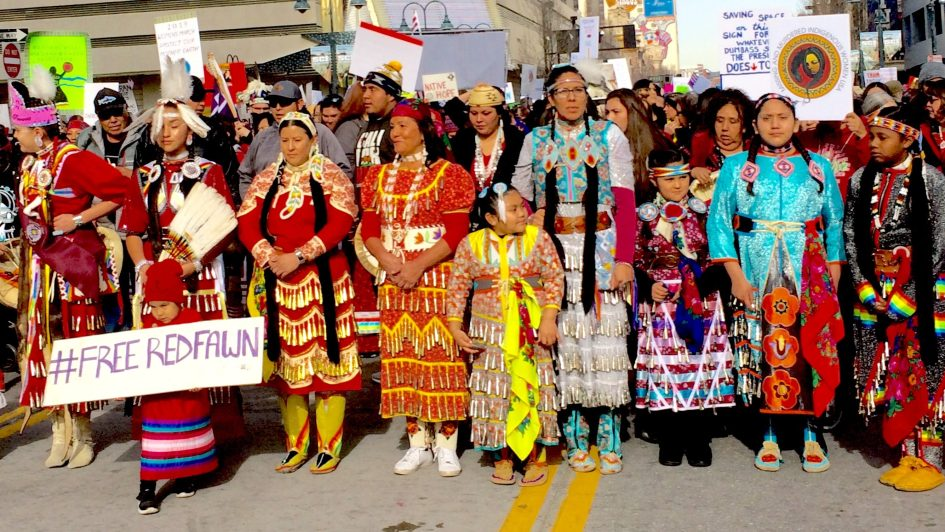 Photo of Native American women at the head of the march--in native dress, especially red