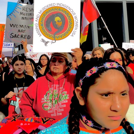 Photo of serious girl in front of a sign about missing and murdered indigenous women