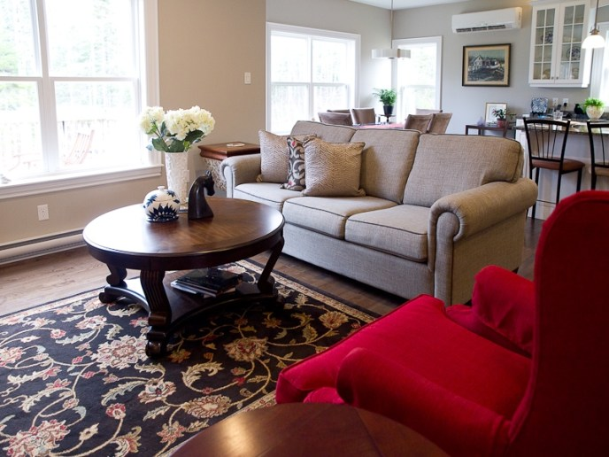 red wingback chairs with grey sofa round table and rug