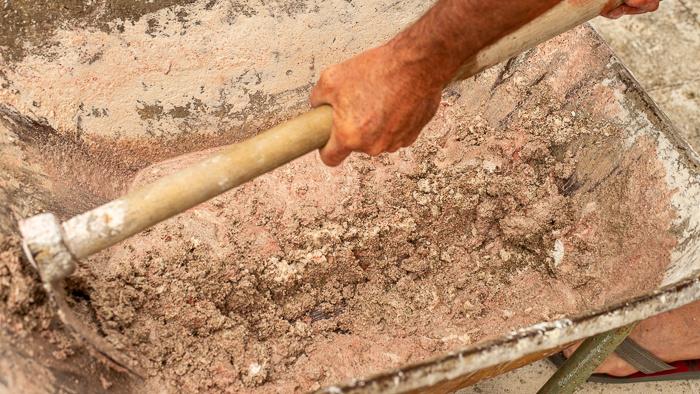 Concrete being mixed in a wheelbarrow.