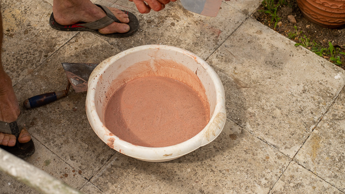 Concrete in the bottom of a bowl being used to hold a concrete flower pot.