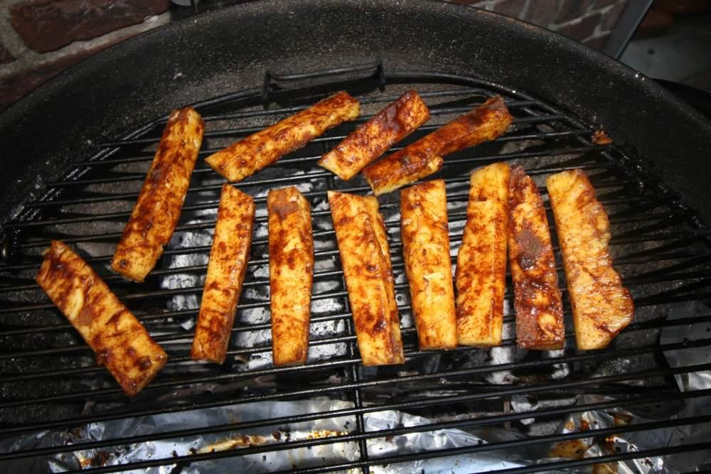 Gegrilde ananas met kaneel en suiker op de barbecue
