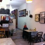 Imagem de uma pequena cafeteria, com algumas mesas, quadros na parede de utensilios de cozinha antigos, um balcão ao fundo com uma maquina de café espresso. O barista está sentado em frente ao balcão, usando um computador.