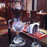 Imagem da cafeteira sifão, formada por 2 globos de vidro presos por um anel central, presos num suporte. No globo inferior, é colocada a água e no globo superior, o café em pó. Não aparece na foto, mas sabe-se que entre os globos há um filtro de pano. Sob o suporte, é colocado uma chama de fogo para o aquecimento da água.