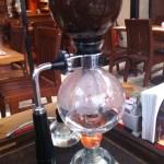 Imagem da cafeteira globinho, ainda com a chama acesa, já quase sem água no compartimento inferior.