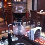 Imagem da cafeteira globinho, já com a chama apagada e retirada de sob a cafeteira. A água misturada com o pó, originando o café na forma líquida, começa a esfriar e desce de volta para o globo inferior.