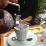 Imagem do café sendo servido na xícara. A parte superior é removida e a parte inferior, junto com a alça do suporte, vira uma jarra.