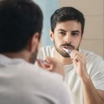 Man practicing self-care by brushing his teeth.