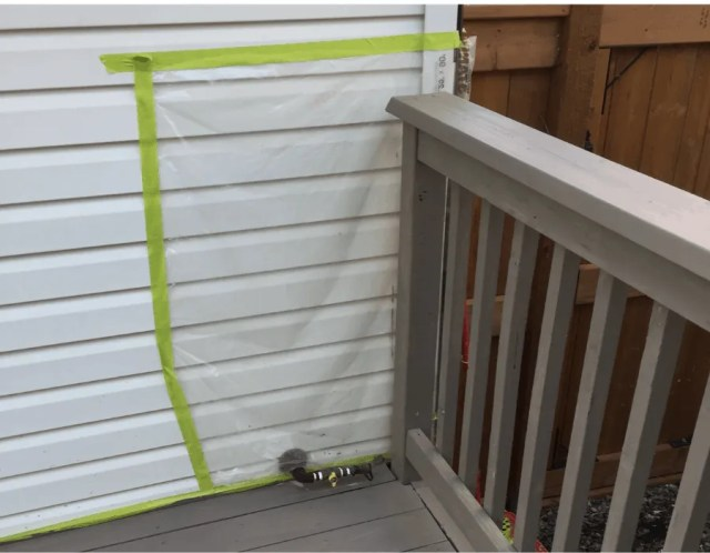 Protect house with plastic when staining deck