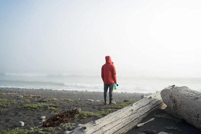 समुद्र तट पर अकेला खड़ा आदमी