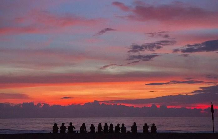एक समुद्र तट द्वारा ध्यान कर रहे लोगों का समूह
