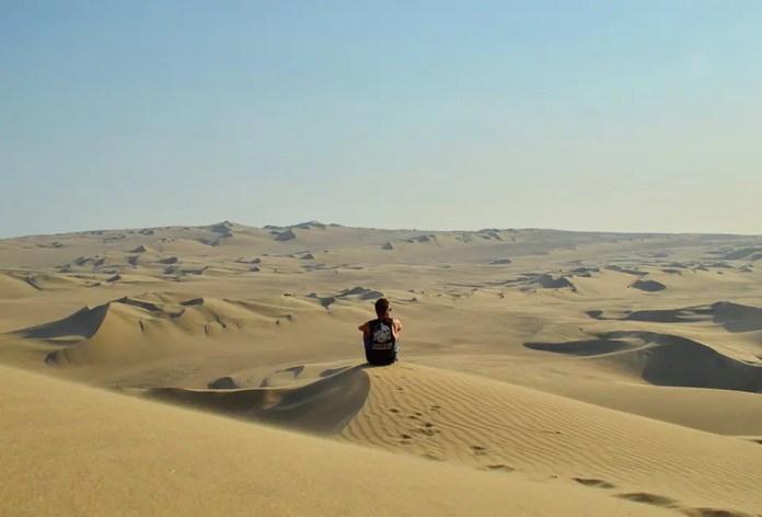 आदमी रेगिस्तान में अकेला बैठा है