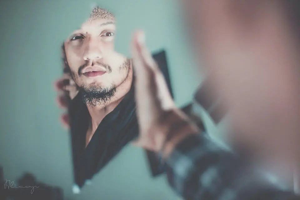 Man looking at a reflection of himself in a broken shard of a mirror