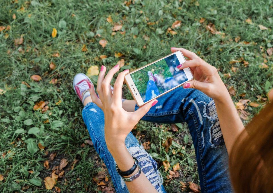 smartphone , navigation sur les réseaux sociaux, jeune femme avec un smartphone dans  les mains.