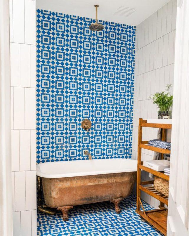mavi ve beyaz Fas çinileri ve bakır ayaklı küvet içeren banyo