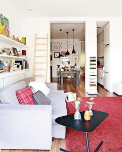 Continuidad de espacios Una columna de obra divide en dos el gran vano que comunica salón, cocina y comedor. La interiorista ha querido dar protagonismo a este elemento arquitectónico al colocar sobre él una librería de pie. Una gran alfombra en rojo llena de vida un salón donde predominan los tonos neutros. Alfombra de pelo largo, de Ikea. Estantería vertical, de La Oca. Sofás, de Sancal. Cojines, de Maison de Vacances y BoConcept.