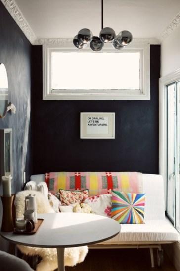 En una caja neutra se dispuso un sofá blaco con mantas y almohadones de colores, generando un cálido y desenfadado comedor.
