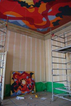 La sala de reuniones está presidida por esta obra de Eske Kath en el techo, en la pared aparece apoyada la pintura sobre la que se han basado para crear el fresco del techo