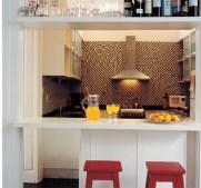 El amoblamiento de termoformado blanco con herrajes de aluminio, las alacenas dobles con vidrio esmerilado y múltiples estantes.
