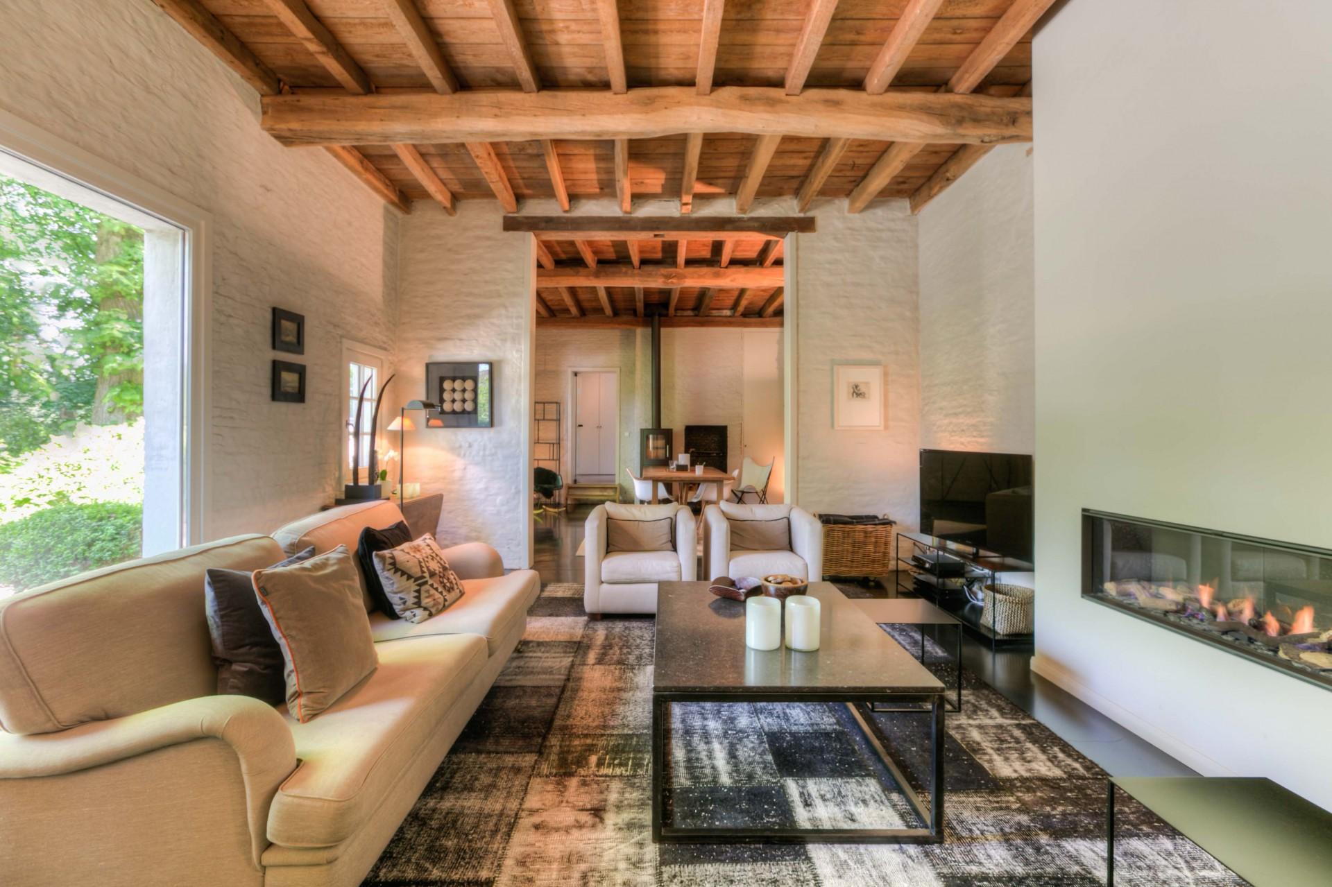 высокий потолок балки гостиная телевизор диван кресло журнальный стол ковер кирпич камин
