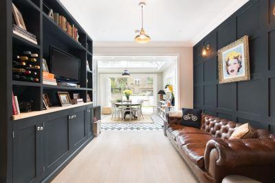 гостиная кожаный диван стеновые панели книжный шкаф телевизор