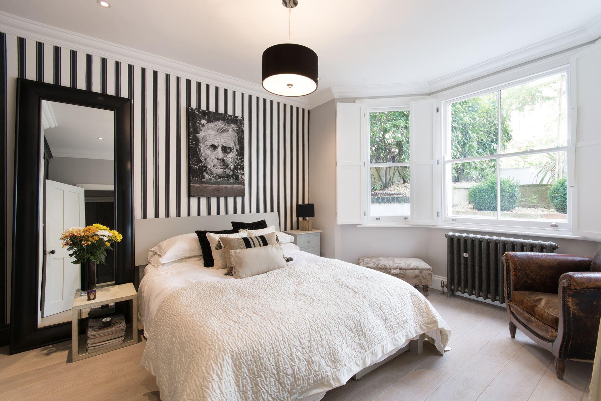 спальня кровать напольное зеркало эркер радиатор обои полоска