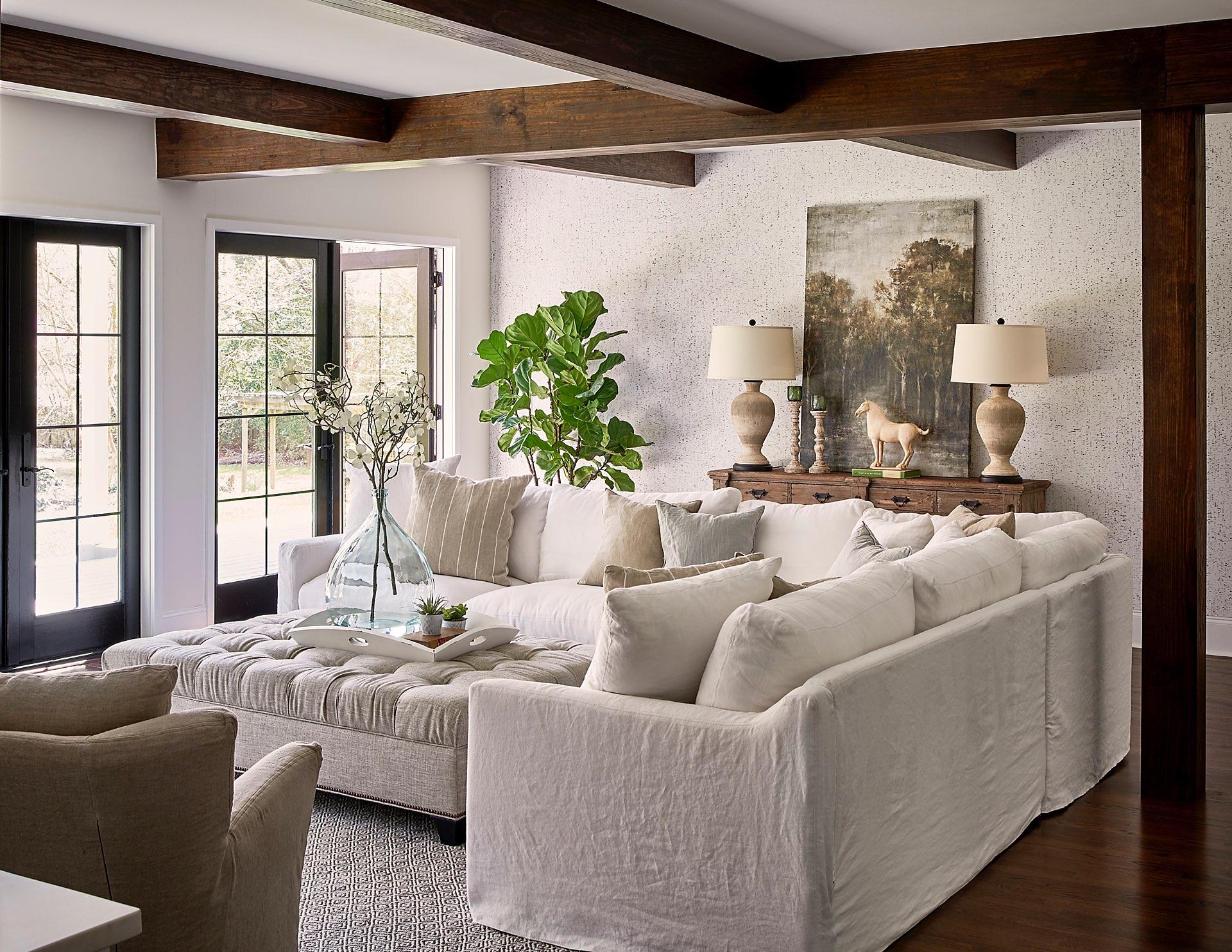 гостиная белые стены деревянный пол мягкая мебель утяжки консоль лампы картина потолок балки французские двери